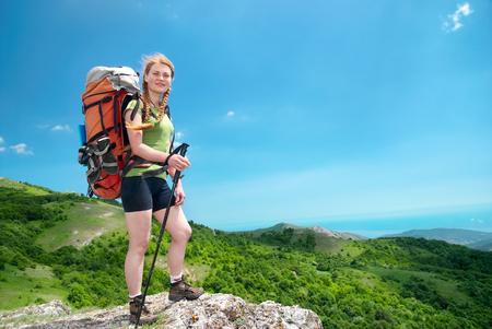 Foto de Happy young hiking woman with backpack on the mountain - Imagen libre de derechos