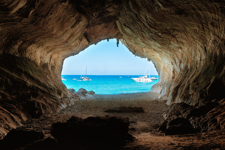 Photo pour View from inside of big cave to the beach and blue sea. Mediterranean coast, Sardinia, Italy. - image libre de droit