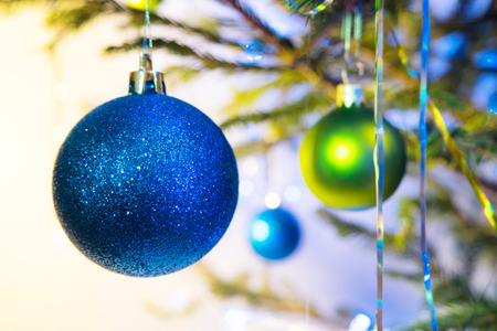 Blue and green holiday balls with christmas tree on white yellow background