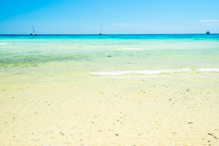 Foto de White sand beach and clear sea water under blue sky. Can be used as summer vacation background - Imagen libre de derechos