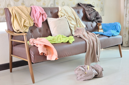 Photo pour Messy clothes scattered on a sofa in living room - image libre de droit