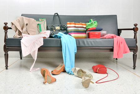 Messy clothes, lady bag and shoes scattered on a leather sofa