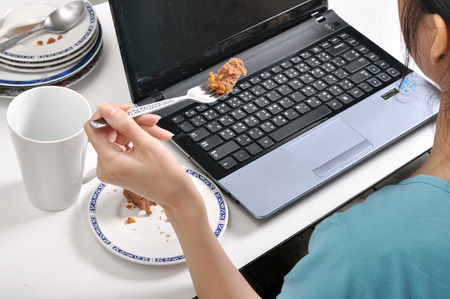 have lunch among stack of dirty plates while busy and using laptop, selective food focus