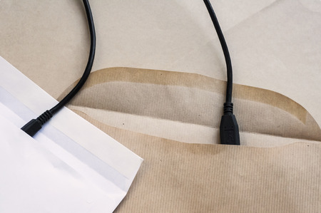 Two paper envelopes symbolically connected with interface cable