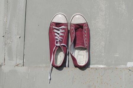 Photo pour Pair of worn out vintage red old canvas sneakers on grey painted tin surface background - image libre de droit