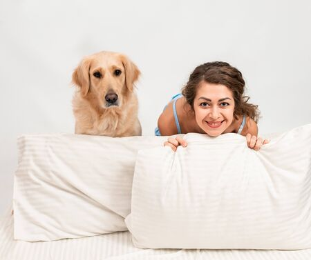 Photo for Cheerful Female woman sleep in pajamas lying in bed with her golden retriever dog. Romantic relationship human and dog concept - Royalty Free Image