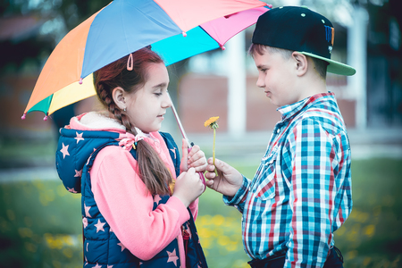 children walk in the park with an umbrella, a boy and a girl amicably walking in the summer with a colored umbrella
