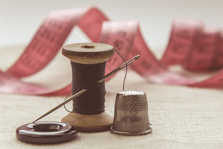 Photo pour the composition of the seamstress, the tailor, the sewing thread and for knitting, the gray thread and the needle and the button - image libre de droit