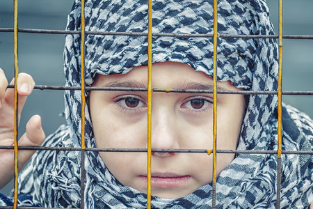Photo pour crying refugee girl from the east in a headscarf - image libre de droit
