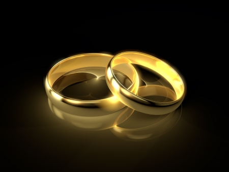 Foto de Two golden wedding rings isolated on black background  - Imagen libre de derechos