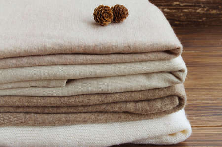 Foto de Close up pf f knitted clothes in nude beige tones. Sweaters and cardigan on a wooden background. Concept of Winter time and Christmas holiday. - Imagen libre de derechos