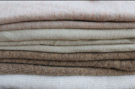 Foto de Close up of sweaters and cardigan. Stack of knitted clothes in nude beige tones for texture or background. - Imagen libre de derechos