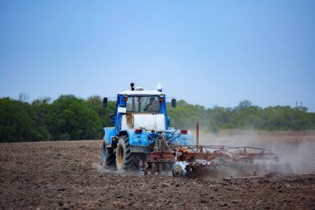 Photo for tractor plows the field with a plow - Royalty Free Image