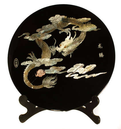 Chinese dragon plays pearl on plate on stand, isolated