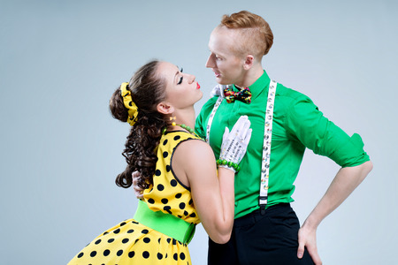 Portrait lovely funny dancer couple dressed in boogie-woogie rock n roll pin up style posing together in studio