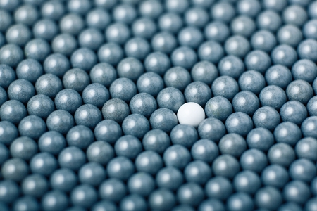 White airsoft ball is among many black balls. Background of 6mm bbs.