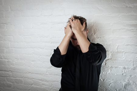 Downcast man holds his head as he suffers from depression and failure. Use it for a headache, money trouble or domestic violence.
