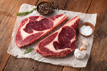 Two fresh raw marble meat, black Angus ribeye steak with spices on a old rustic table. Raw beef on a wooden background.