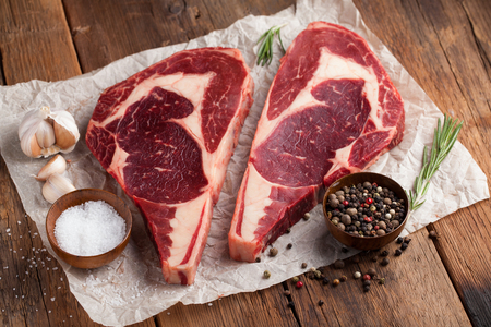 Two fresh raw marble meat, black Angus ribeye steak with spices on a old rustic table. Raw beef on a wooden background. Top view