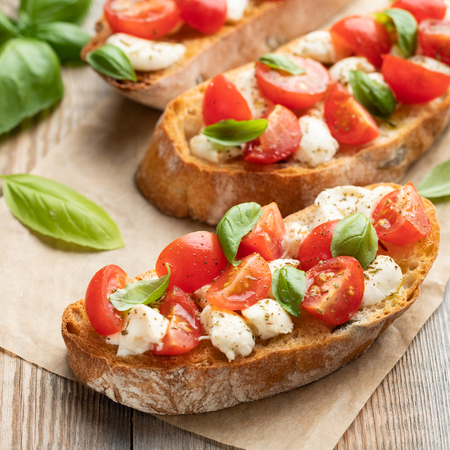 Bruschetta with tomatoes, mozzarella cheese and basil on a old rustic table. Traditional italian appetizer or snack, antipasto.