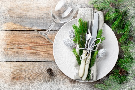 Foto de Christmas table setting with christmas decorations. White plate, Cutlery, fir cones and towel with snowflakes on old rustic wooden background. Frosty the snow frame. Top view, copy space. Flat lay. - Imagen libre de derechos