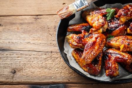 Foto de Baked chicken wings in barbecue sauce in a cast iron pan on an old wooden rustic table. - Imagen libre de derechos