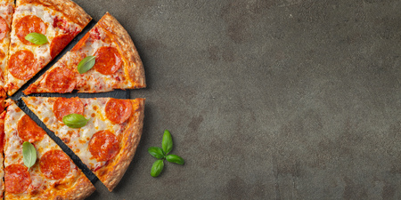 Foto de Tasty pepperoni pizza with basil on brown concrete background. Top view of hot pepperoni pizza. With copy space for text. Flat lay. - Imagen libre de derechos