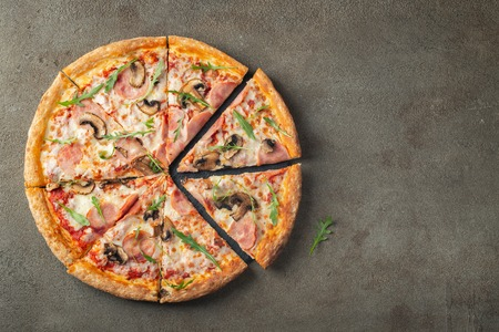 Foto de Italian fast food. Delicious hot pizza with ham and champignons sliced and served on brown concrete table, close up view. Menu photo. Top view with copy space. Flat lay. - Imagen libre de derechos