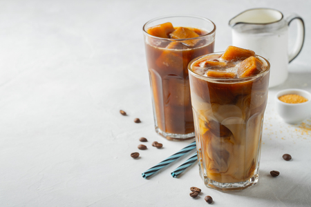 Foto de Ice coffee in a tall glass with cream poured over and coffee beans. Cold summer drink on a light background. With copy space. - Imagen libre de derechos