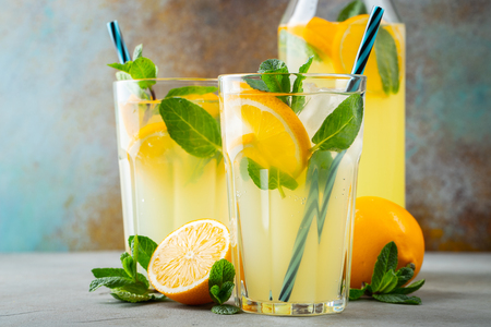 Photo pour Two glass with lemonade or mojito cocktail with lemon and mint, cold refreshing drink or beverage with ice on rustic blue background. - image libre de droit