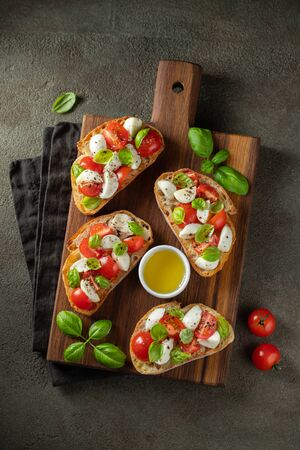 Photo for Bruschetta with tomatoes, mozzarella cheese and basil on a cutting board. Traditional italian appetizer or snack, antipasto. Top view. Flat lay. - Royalty Free Image