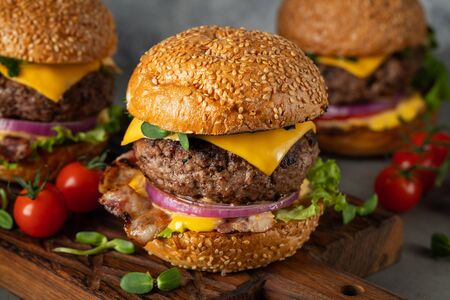 Photo pour A set of homemade delicious burgers of beef, bacon, cheese, lettuce and tomatoes on a light concrete background. Fat unhealthy food close-up - image libre de droit