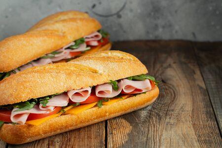 Photo pour Two Long baguette Sandwiches with arugula, slices of fresh tomatoes, ham and cheese - image libre de droit