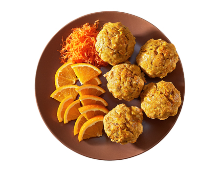 Carotte muffins served on the plate with orange slices, top view, isolated.
