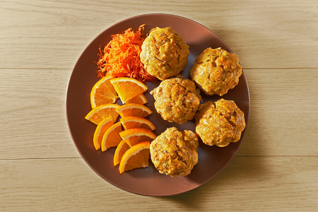 Carotte muffins served on the plate with orange slices, top view