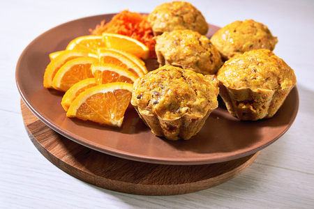 Carotte muffins served on the plate with orange slices.