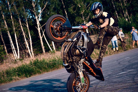 Photo pour Moscow, Russia - Jul 12, 2020: Moto rider making a stunt on his motorbike. Stunt motorcycle rider performing motorcycle show. Motorcyclist making doing a difficult and dangerous stunt on his motorbike - image libre de droit