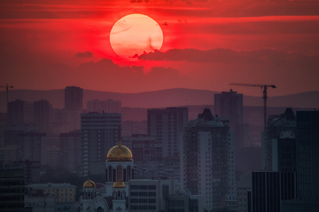 Photo pour Ekaterinburg, Russia - Jule, 2018: Telephoto lens panoramic shot of cityscape view megalopolis during sunset with giant sun at summer evening - image libre de droit