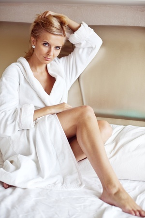 An image of a young pretty woman in a white bathrobe