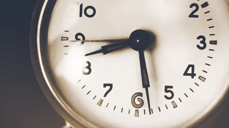 Foto de The old clock on the dial shows half-past eight in the morning. Fast-moving time and the past. Memories. - Imagen libre de derechos