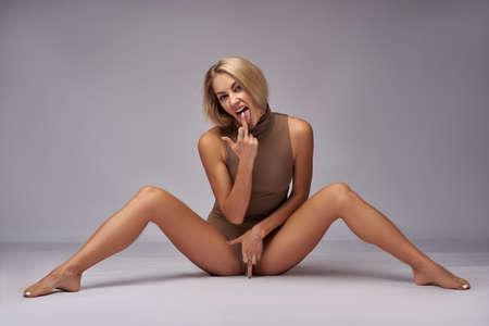 Photo pour Beautiful girl blonde in a bodysuit in the studio white background - image libre de droit