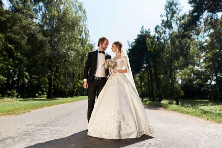 Photo pour beautiful wedding couple posing by the green trees - image libre de droit
