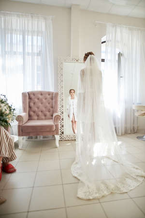 Photo pour beautiful morning of the bride. charming bride in lingerie is standing and looking at the mirror. - image libre de droit