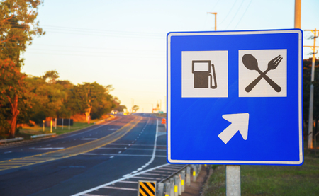 Photo for Road sign at the roadside signaling a gas station and food services on highway. Blue board with an arrow informing services straight ahead. - Royalty Free Image