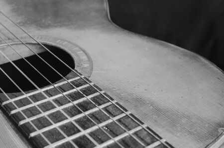 Details of an old acoustic guitar, the body curves, sound hole, frets and nylon strings. Wooden acoustic guitar, worn out and dusty. Black and white, macro photo, with depth of field.