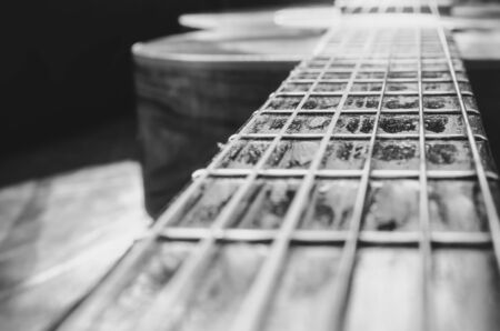 Perspective photo of the neck of an old acoustic guitar and the body unfocused on the background. Focus on a part of the neck between frets. Black and white macro photo with depth of field.