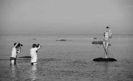 Photographers and nude model on the beach  Photoshooting on