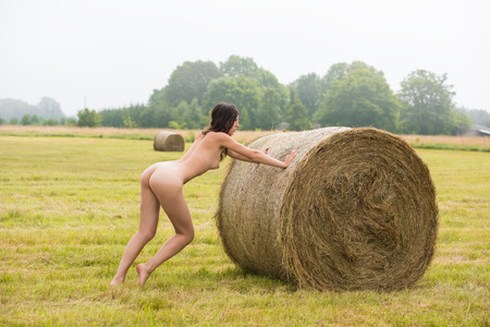 Young nude woman posing near haystack on the field