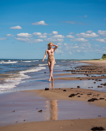 Young nude woman posing on a sandy beach neat the sea. Sexy blonde enjoying hot summer day outdoors