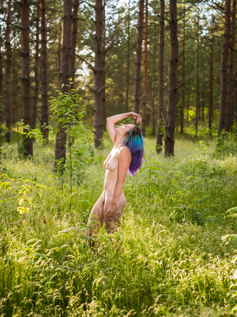 Romantic image of young naked woman posing outdoors. Enjoying summer time